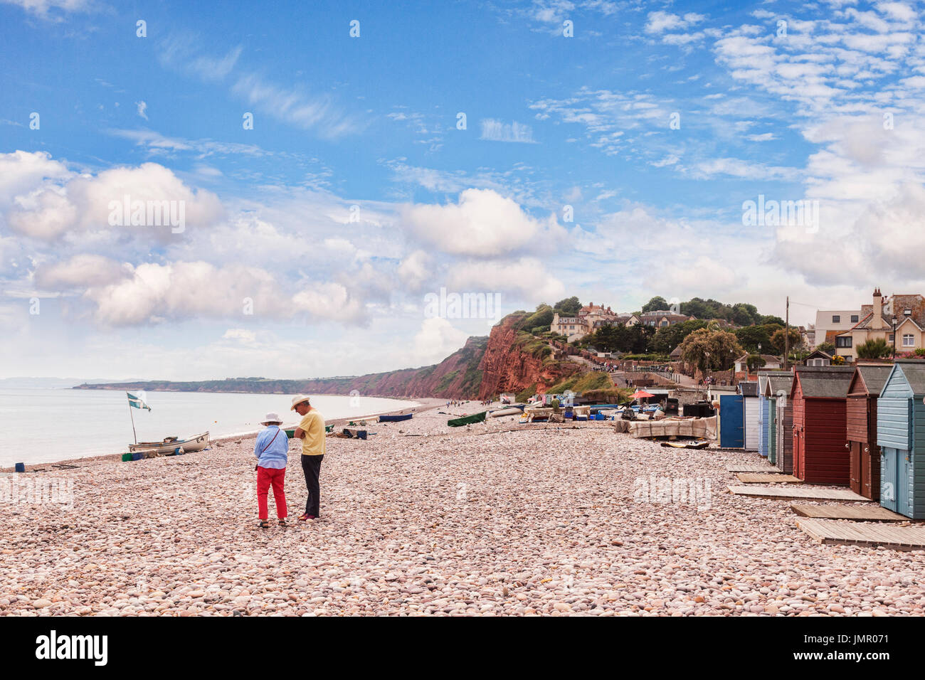 26 June 2017: Budleigh Salterton, East Devon, England, UK - Senior couple on the pebble beach at Budleigh Salterton, on a bright summer day with blue  - Stock Image