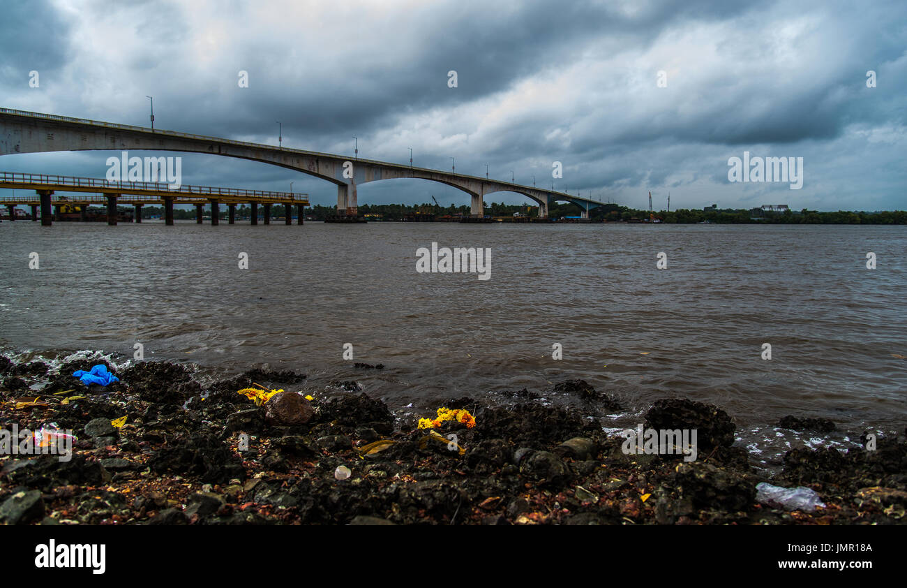 Trash dumped shore of a river with a long bridge in the backgound - Stock Image