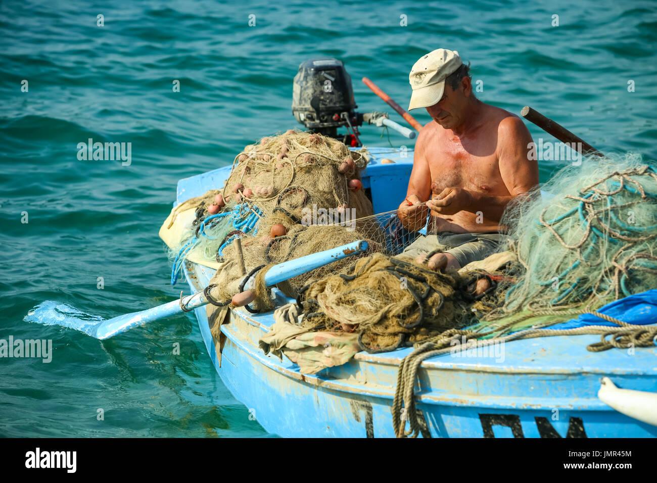 NJIVICE, CROATIA - JUNE 24, 2017 : A fisherman in an anchored boat checking the fishing net in Njivice, Croatia. - Stock Image