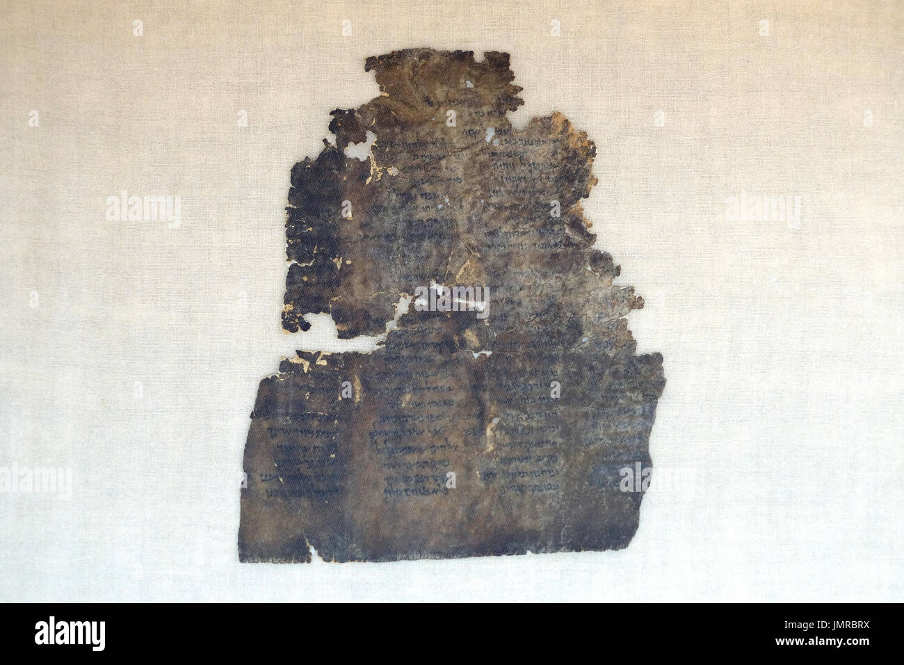 A fragment of Dead Sea Psalms scroll written in Hebrew found in Qumran caves in the preservation laboratory of the Stock Photo