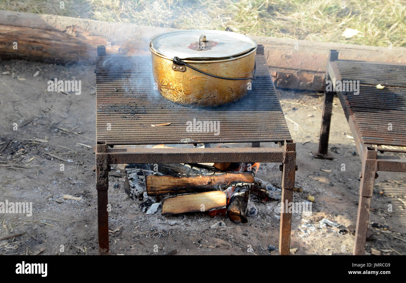 Camp food being cooked on a camp fire. - Stock Image