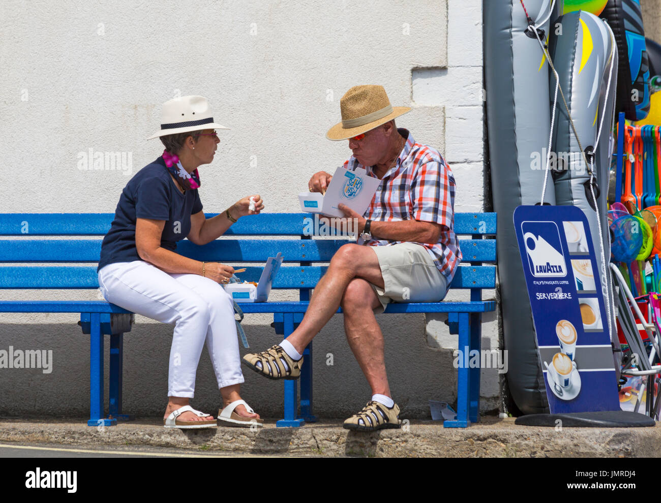 Couple sitting on bench eating fish and chips at Lyme Regis, Dorset in July Stock Photo