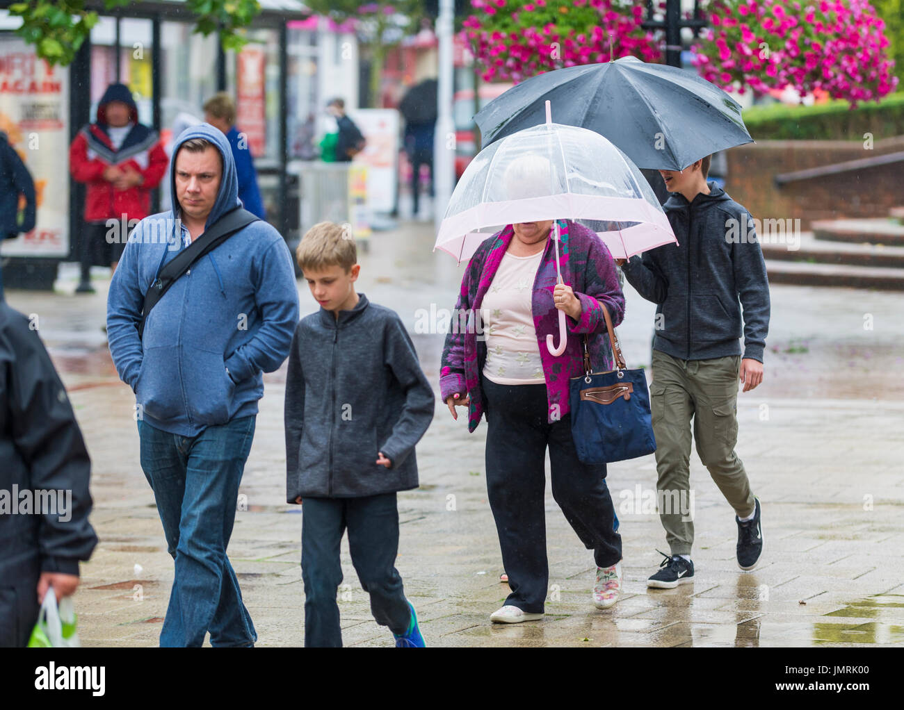 Family walking in the rain holding umbrellas in a shopping centre. - Stock Image