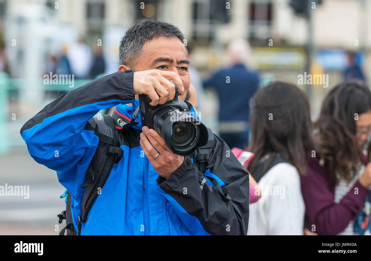 Male Japanese tourist taking photos with a DSLR camera. - Stock Image