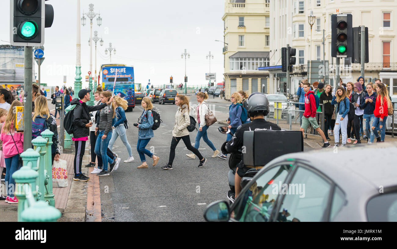 People crossing road at a Pelican crossing after traffic lights for cars have turned green. - Stock Image
