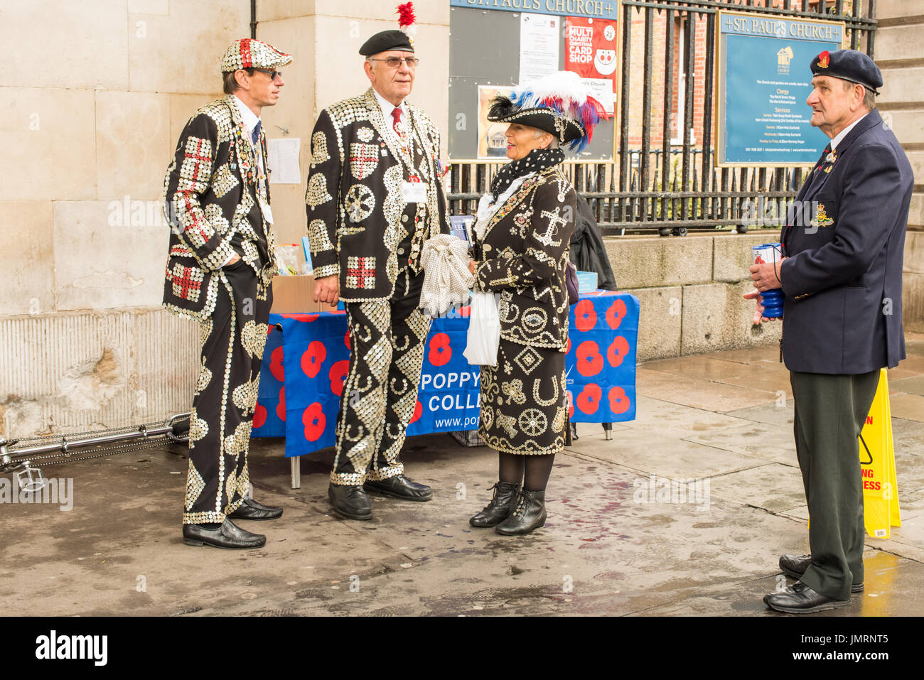 Pearly Kings and a Pearly Queen helping to raise money for the poppy appeal with an ex-serviceman in his beret and blazer in London. - Stock Image