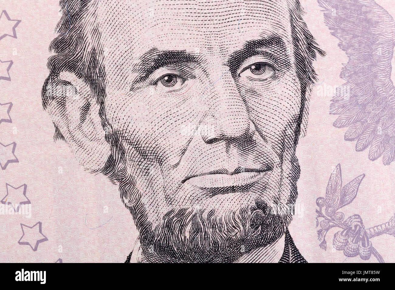 Macro portrait of Abraham Lincoln on five U.S. dollar bill. - Stock Image
