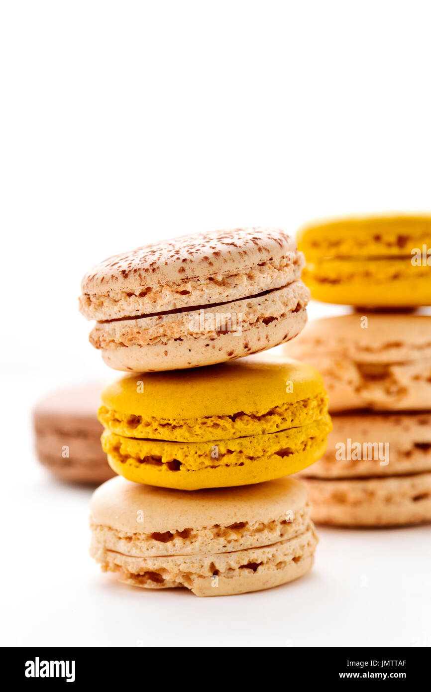 some stacks of appetizing macarons with different colors and flavors on a white background - Stock Image