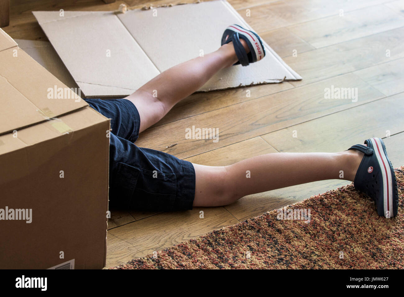 The legs of a young boy sticking out of a cardboard box. - Stock Image