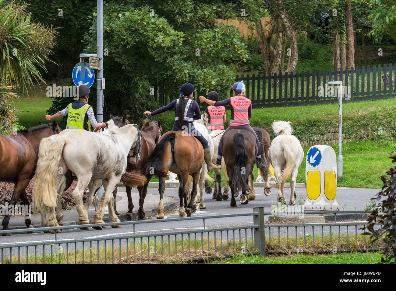 Horse riders riding on public roads. - Stock Image