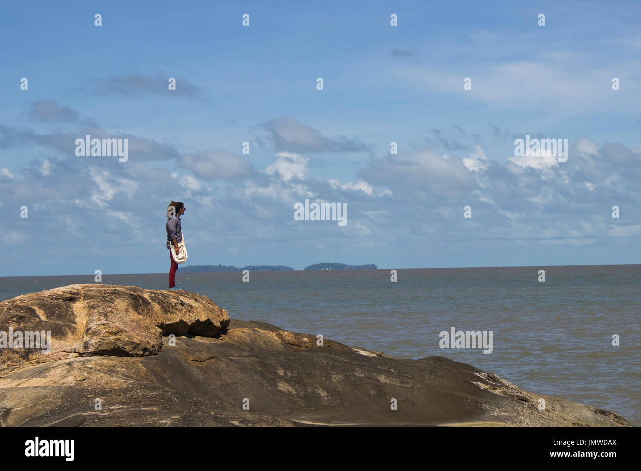 A man standing on a rock  on the background of Salvation's islands in Kourou, French Guiana - Stock Image