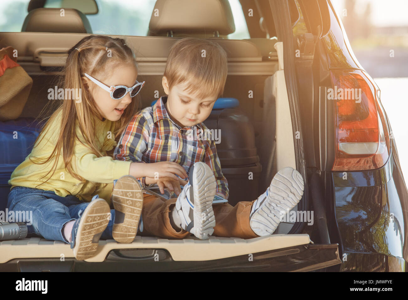 Travel by car family together brother and sister sitting in a trunk - Stock Image