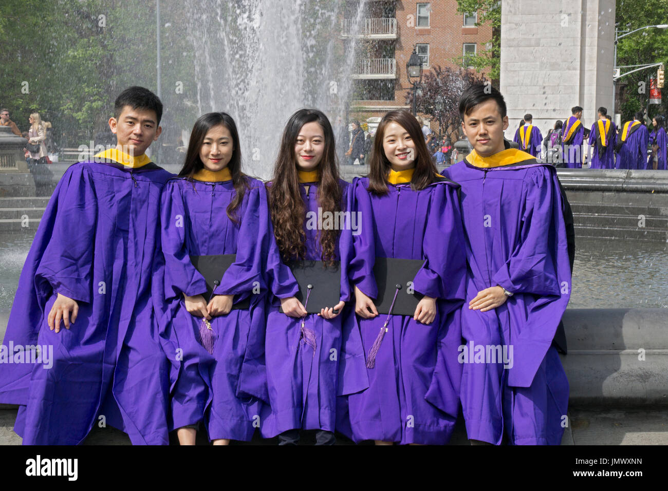 A group of Chinese students at NYU celebrating their graduation in Washington Square Park in Greenwich Village, Manhattan, New York City - Stock Image