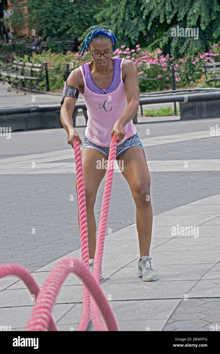 An attractive fit muscular young lady working out on the battle ropes during an outdoor fitness class in Washington Square Park in Greenwich Village, - Stock Image