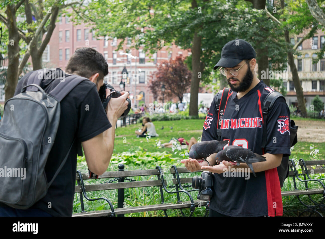 A tourist in Washington Square Park feeds pigeons from his hand while a friend commemorates it with a photo. New York City. - Stock Image