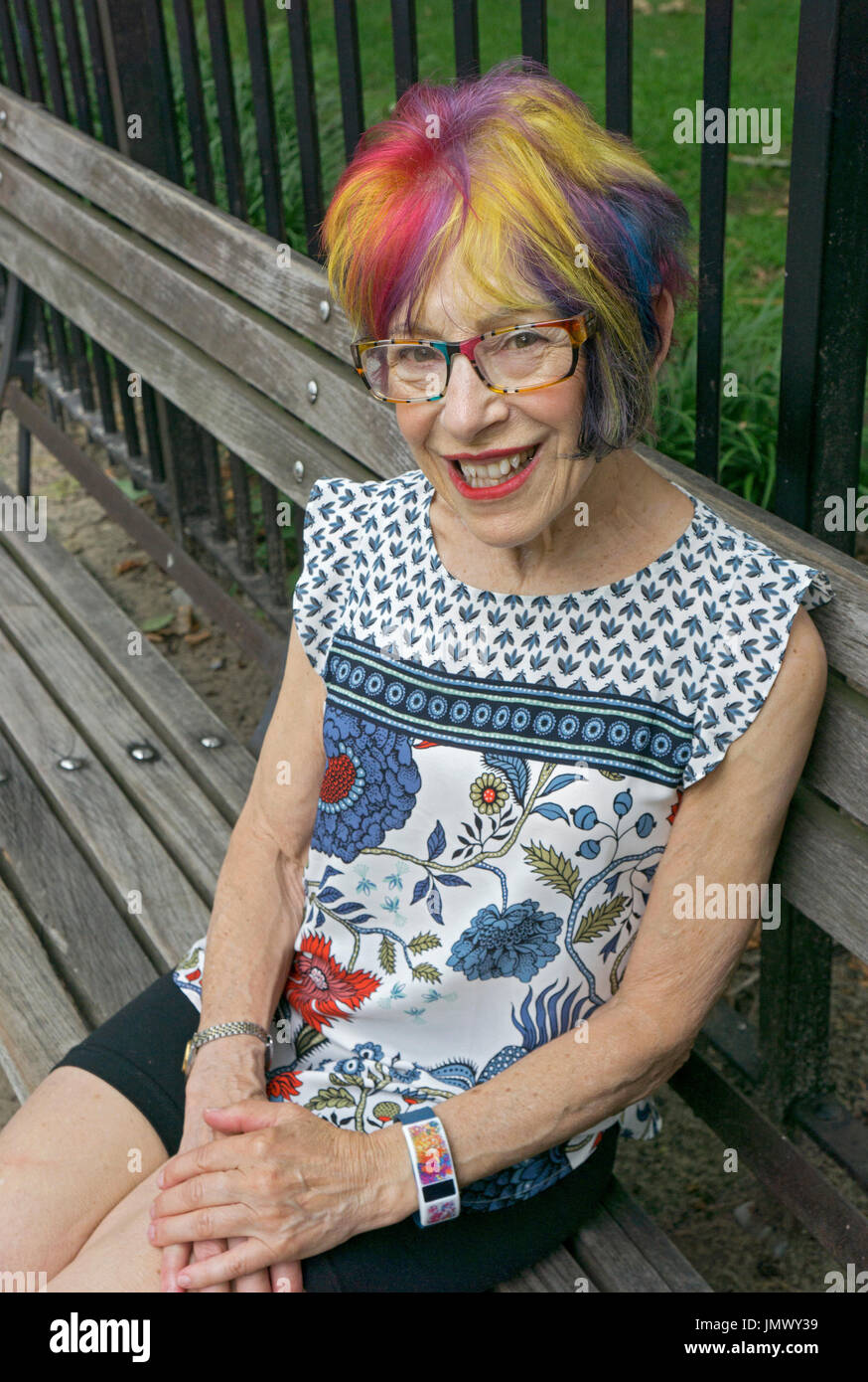 Portrait of an attractive youthful woman in her mid seventies with a modern multicolored hairdo. In Greenwich Village, New York City. - Stock Image
