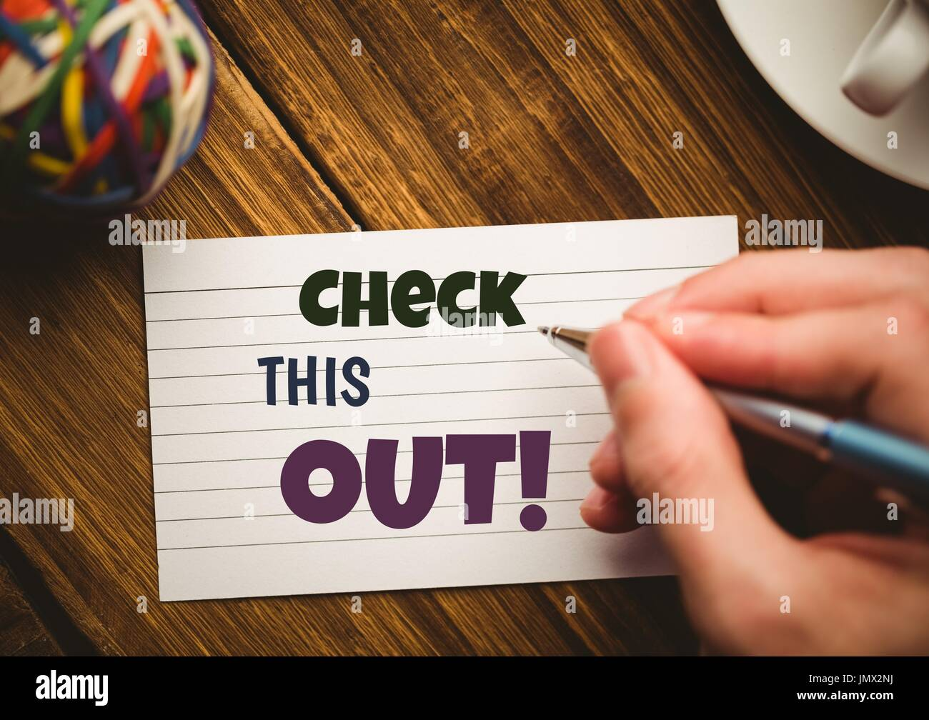 Digital composite of Check this out  text written on note on table - Stock Image