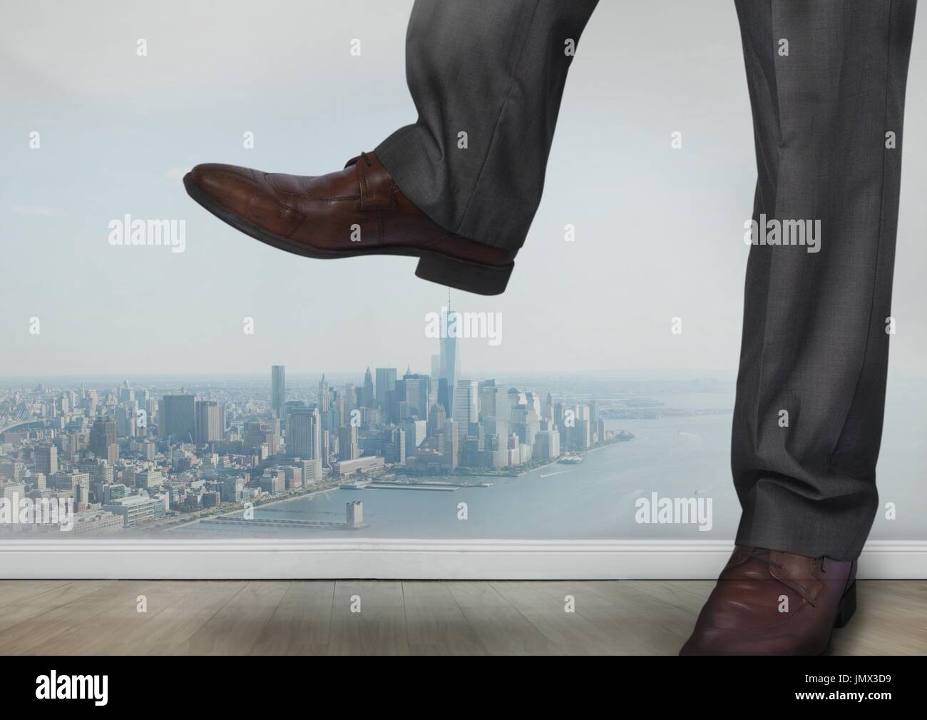 Digital composite of Businessman's feet and shoes stamping on city - Stock Image