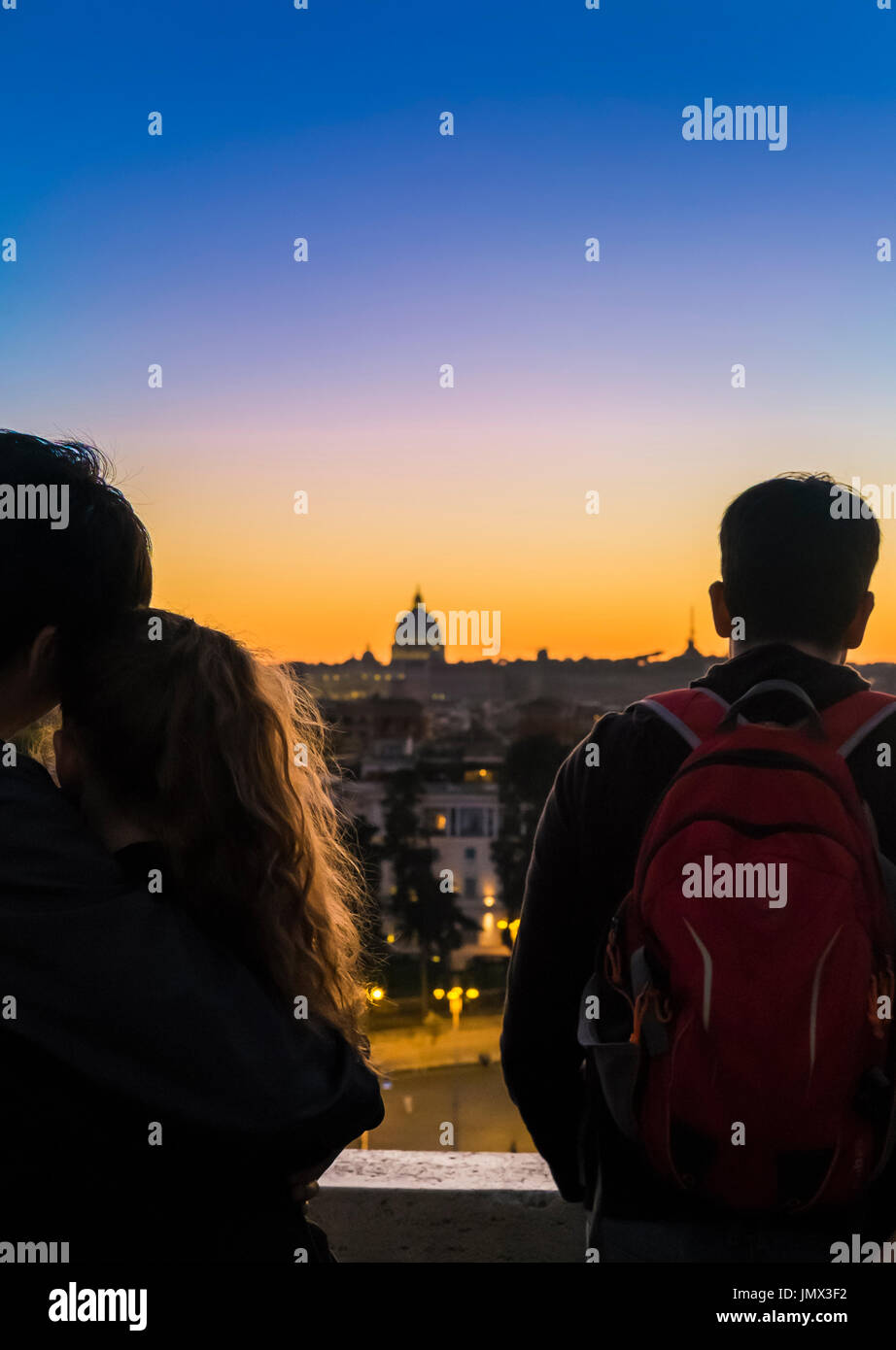 young couple looking at st peter´s  basilica at dusk, seen from pincian hill in villa borghese gardens, rome, lazio, italy - Stock Image