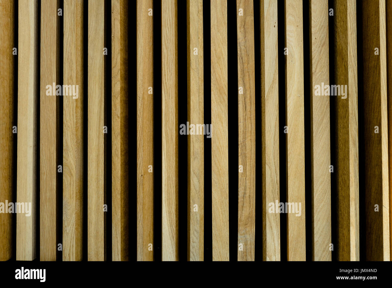 Lengths of vertical golden oak panels making a symmetric structure of wall cladding - Stock Image