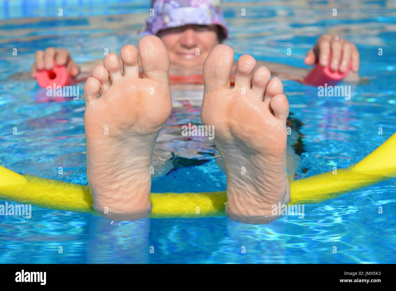 Keeping cool! Woman floating on two pool noodles in a swimming pool. Just chilling. - Stock Image