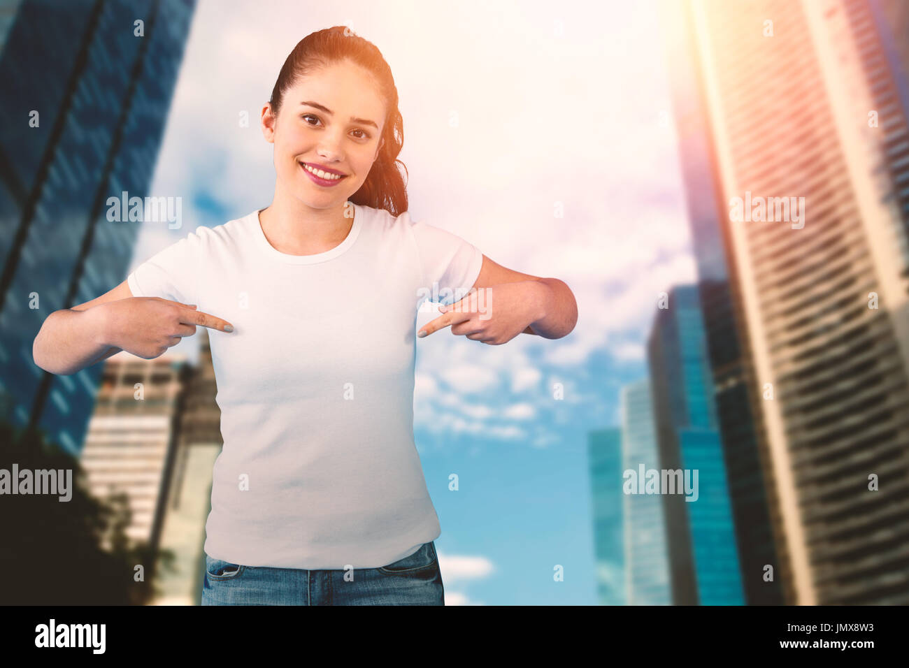Portrait of smiling brunette woman in front of white background against city Stock Photo