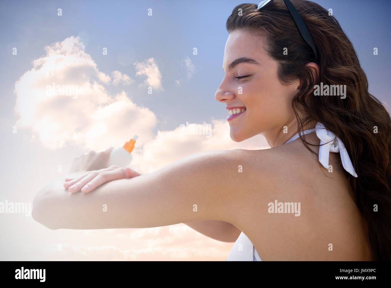 Beautiful women applying suncream against colored sky with clouds - Stock Image