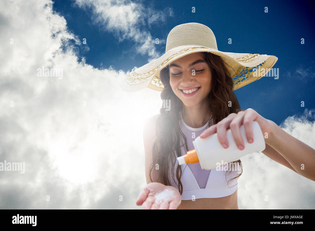 Beautiful women applying suncream and wearing hat against view of beautiful sky and clouds - Stock Image