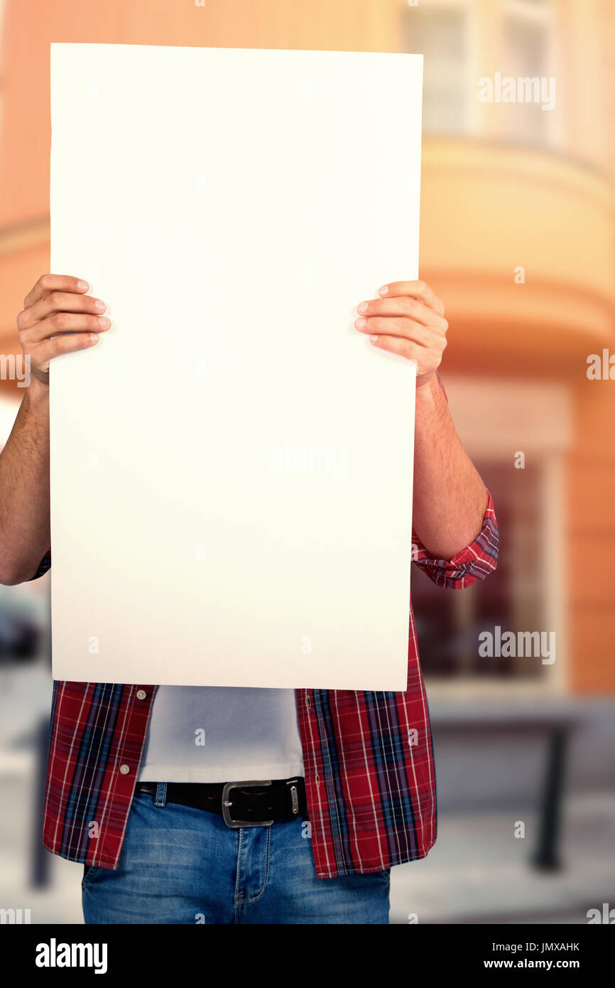 Male model holding blank placard against cafe building exterior on street - Stock Image