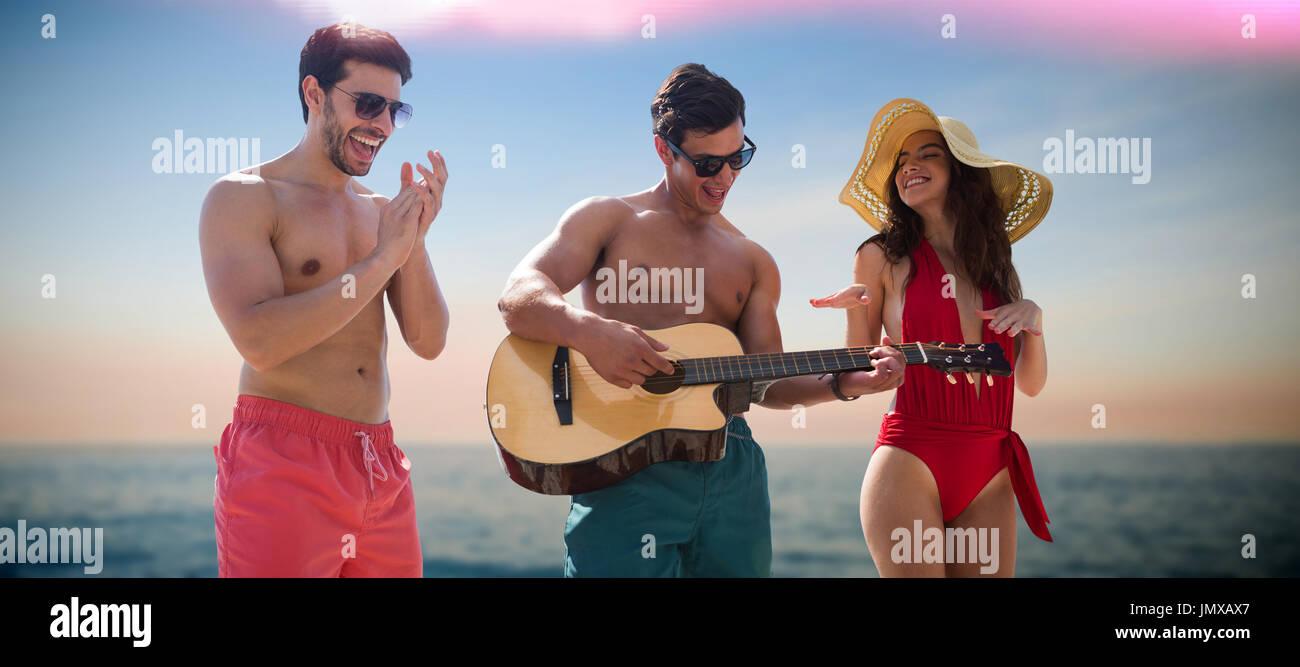 Friends playing music in swimwear against idyllic view of sea Stock Photo