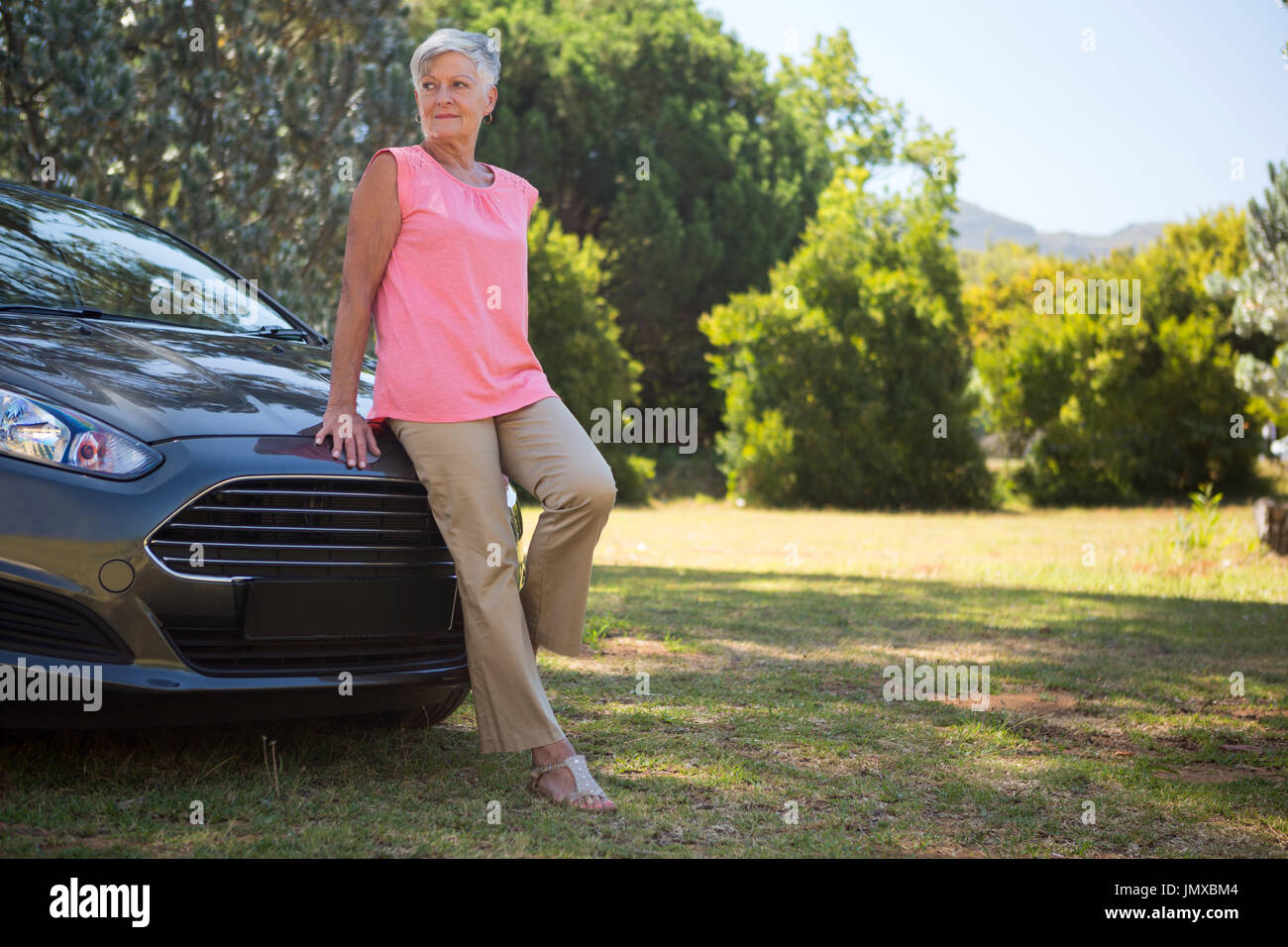 Thoughtful senior woman leaning on her new car Stock Photo