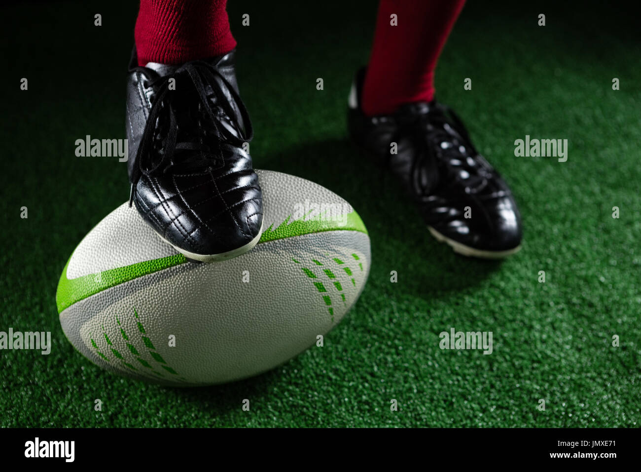 Low section of sportsperson stepping on rugby ball while plying rugby - Stock Image