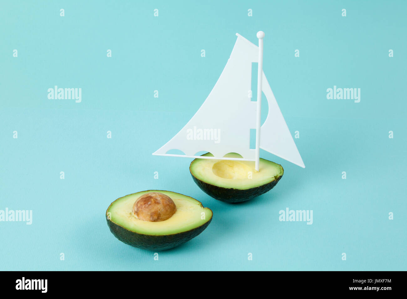 avocado half with white sail on a turquoise background. minimal and quirky color still life photography - Stock Image