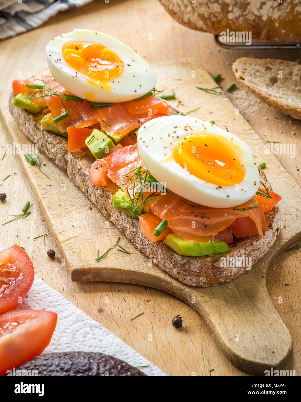 Toasted sourdough bread with Tomato, Avocado - Stock Image