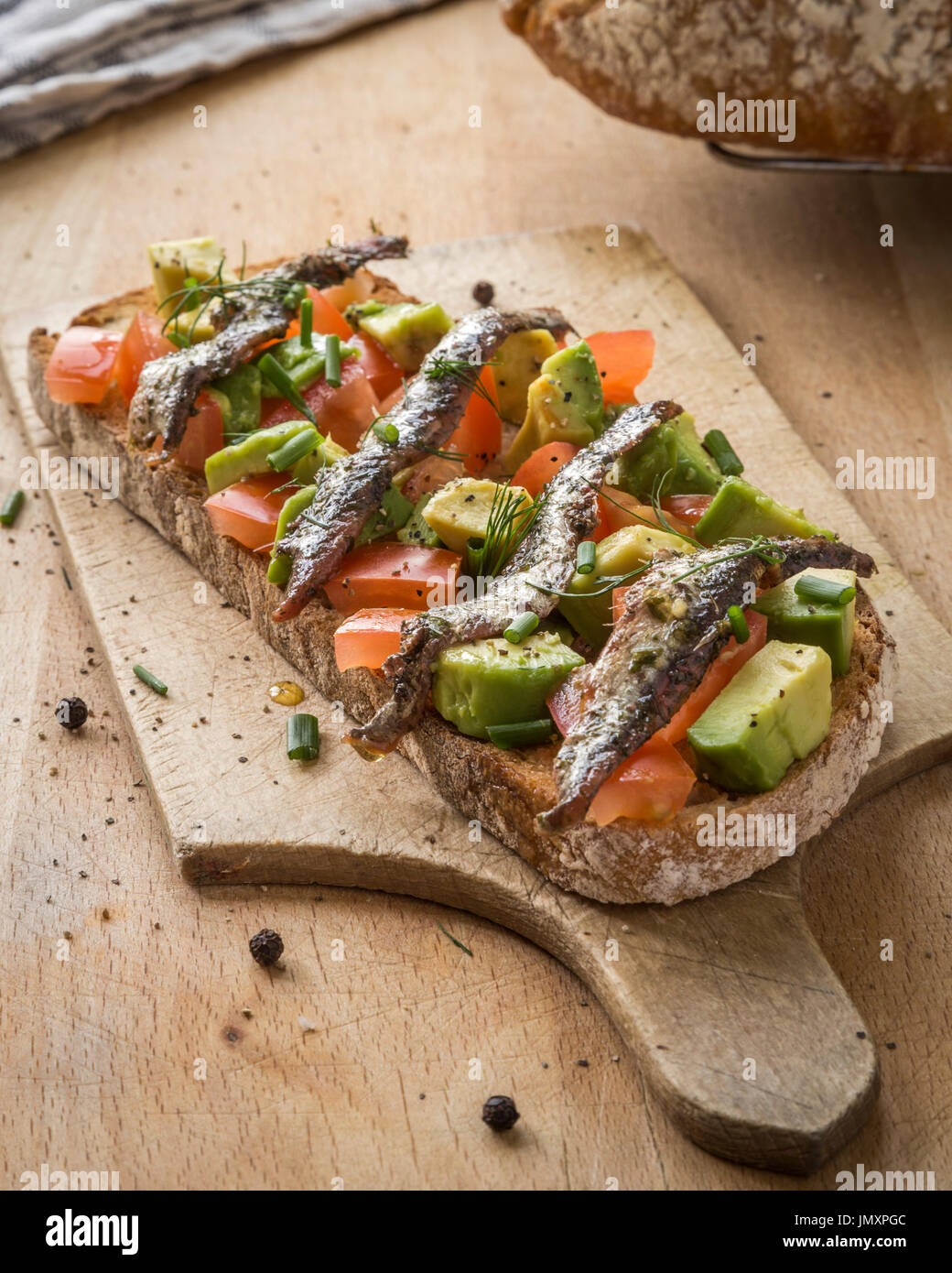 Toasted sourdough bread with Tomato, Avocado and Anchovies. Stock Photo