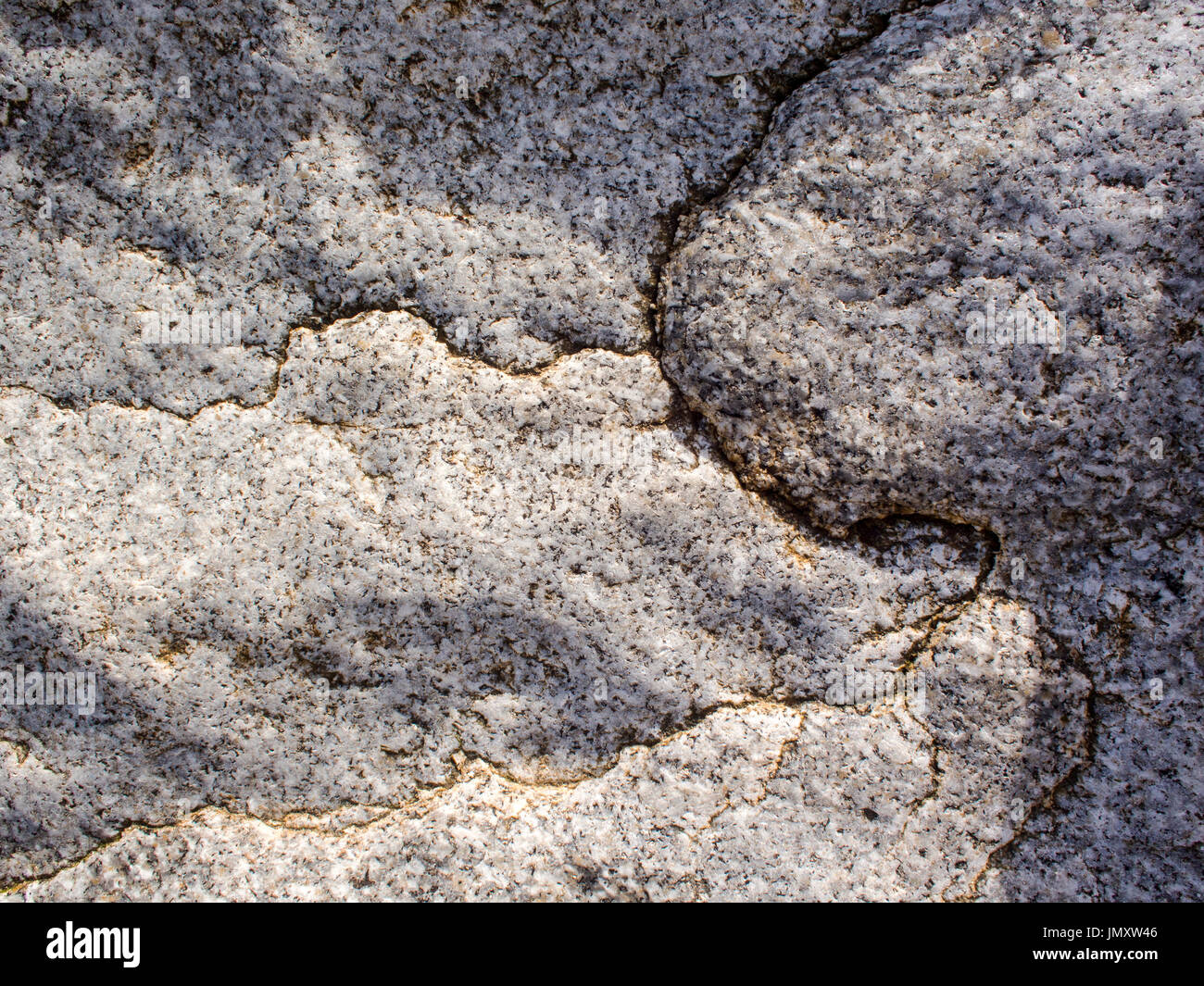 Detail of cracks in the weathered surface of granite rock on a seashore. Stock Photo