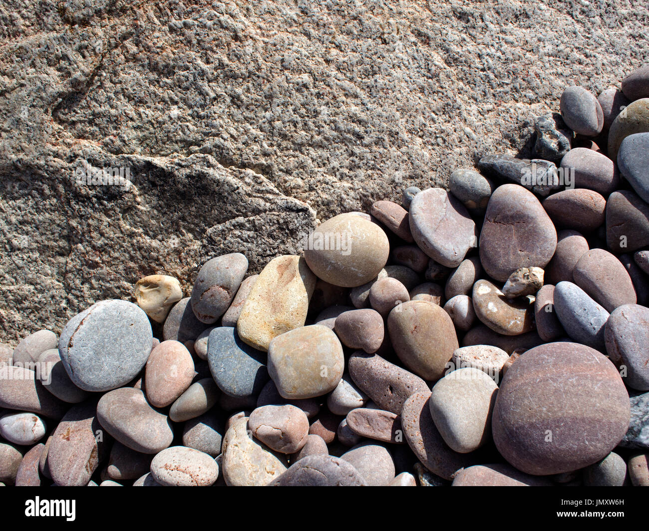 Worn and rounded pebbles forming interesting patterns in the gaps between the rocks of a rock armour groyne on a Stock Photo