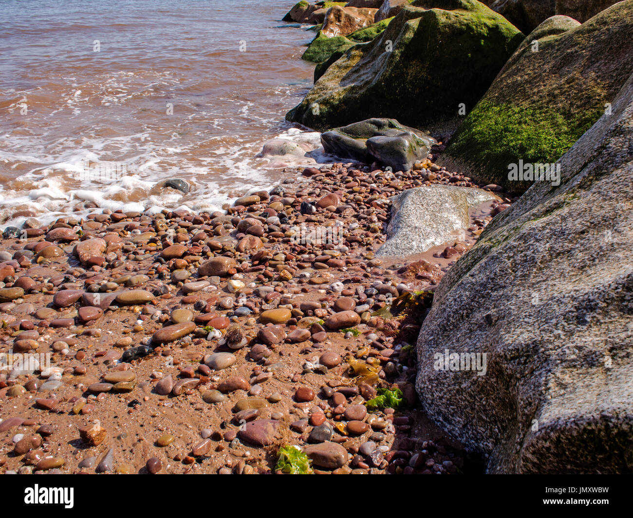 Water laps over smooth, rounded pebbles on a beach, showing gradation of deposits alongside a rock armour groyne. Stock Photo