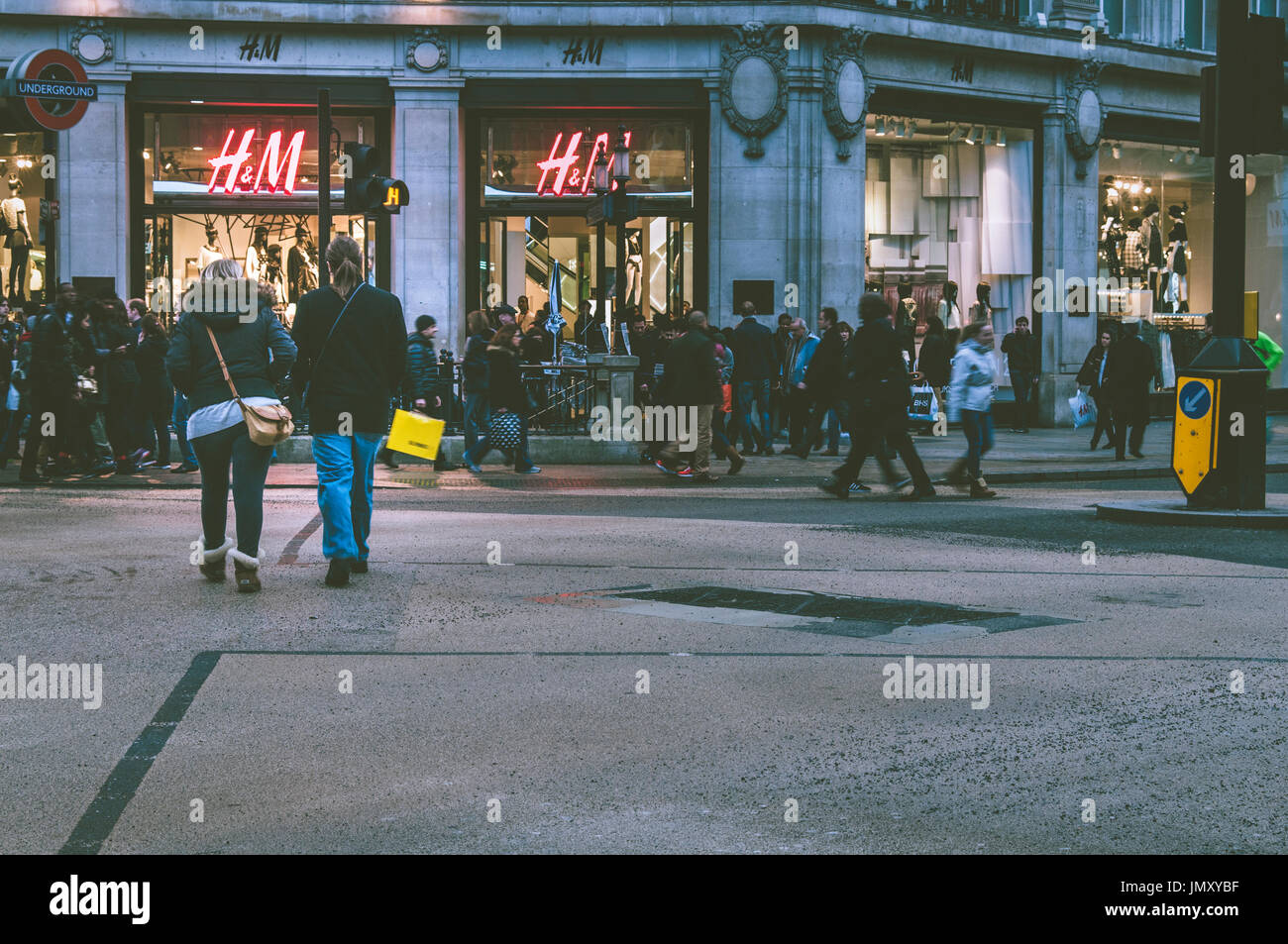 Shoppers walk past H&M shop located on Oxford street, London. - Stock Image