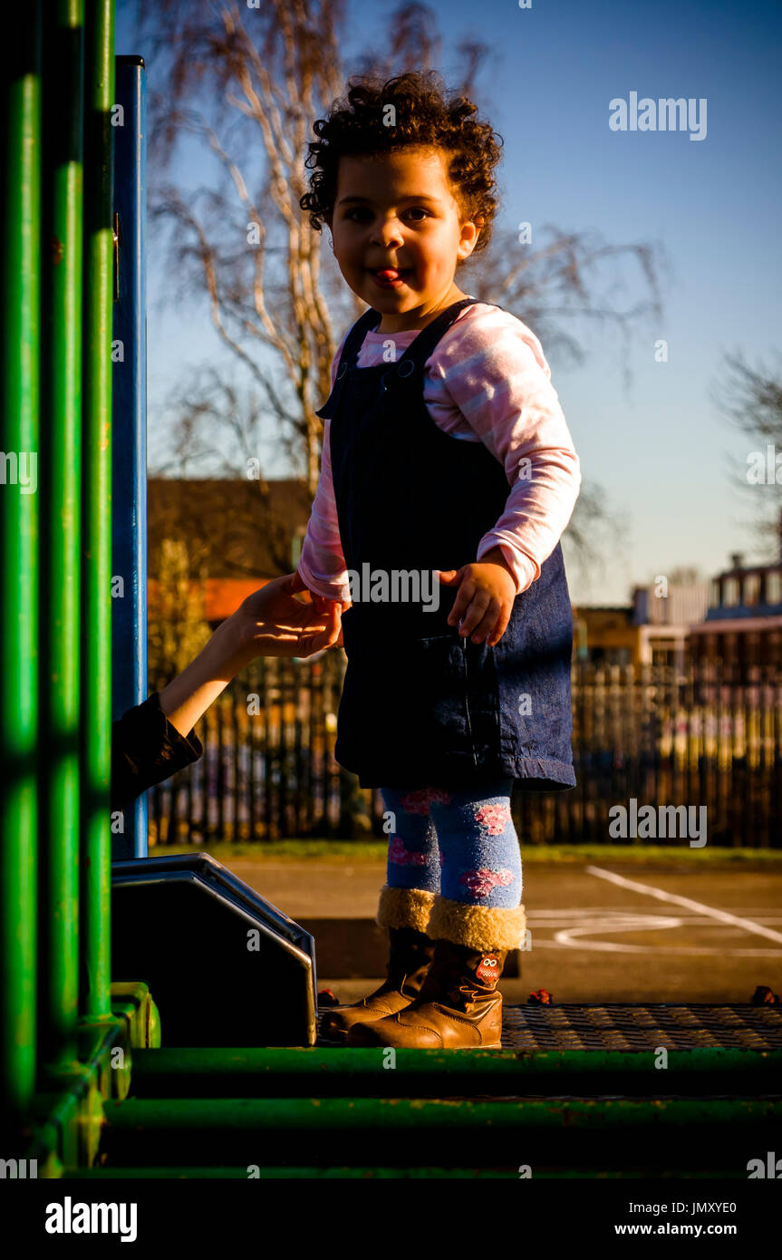 Portrait of a toddler who is playing in the playground. She is about to climb on the monkey bars Stock Photo