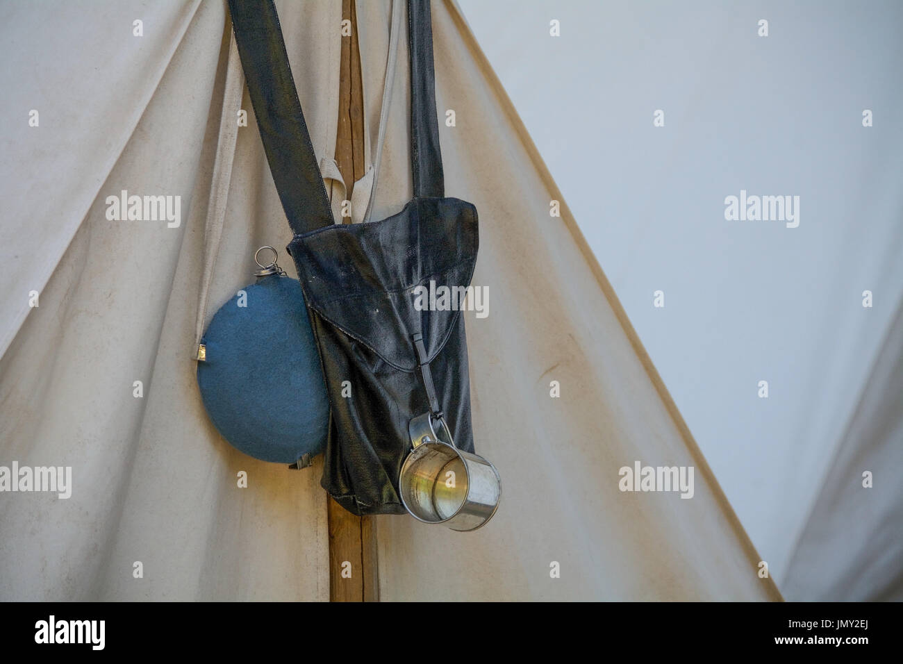 2508c98b2d Canteen, leather backpack and tin cup hanging at the entrance of a ...