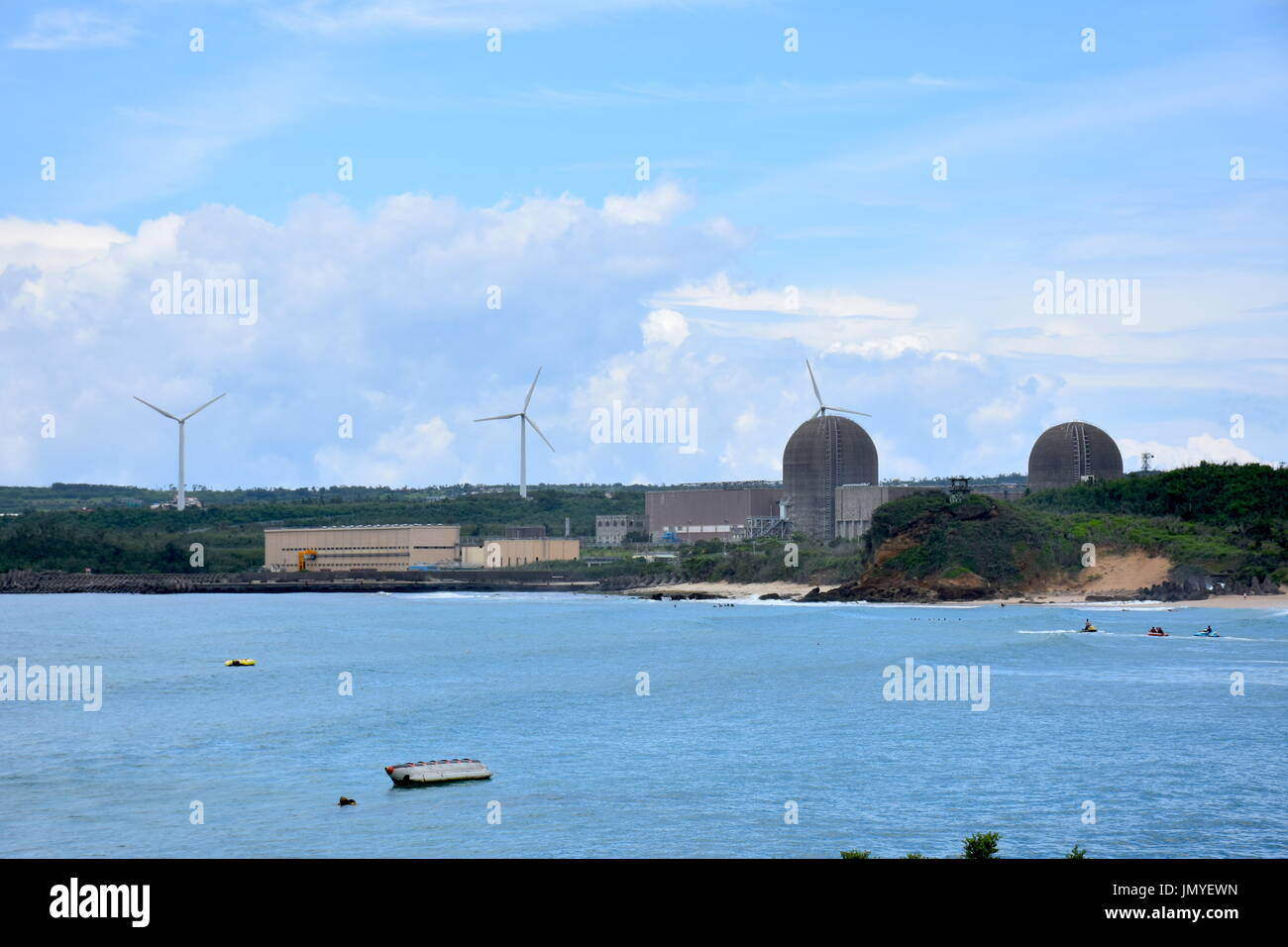 This is a nuclear power plant in South Taiwan with three wind powered windmills behind them to make the public happy. - Stock Image