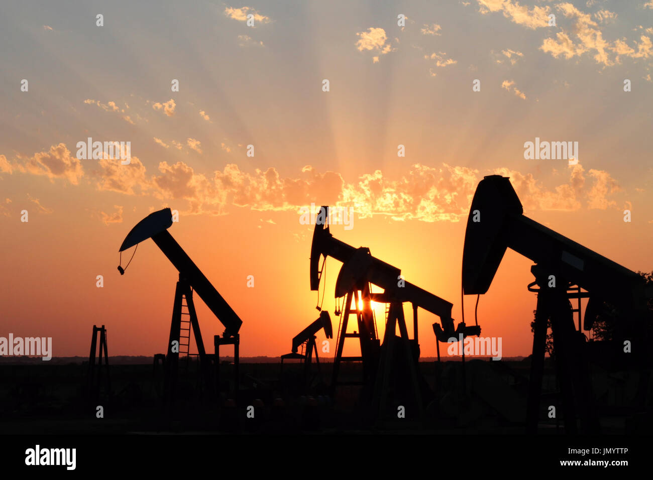 Several oil rigs stand in silhouette with a brilliant sunset in the background. - Stock Image
