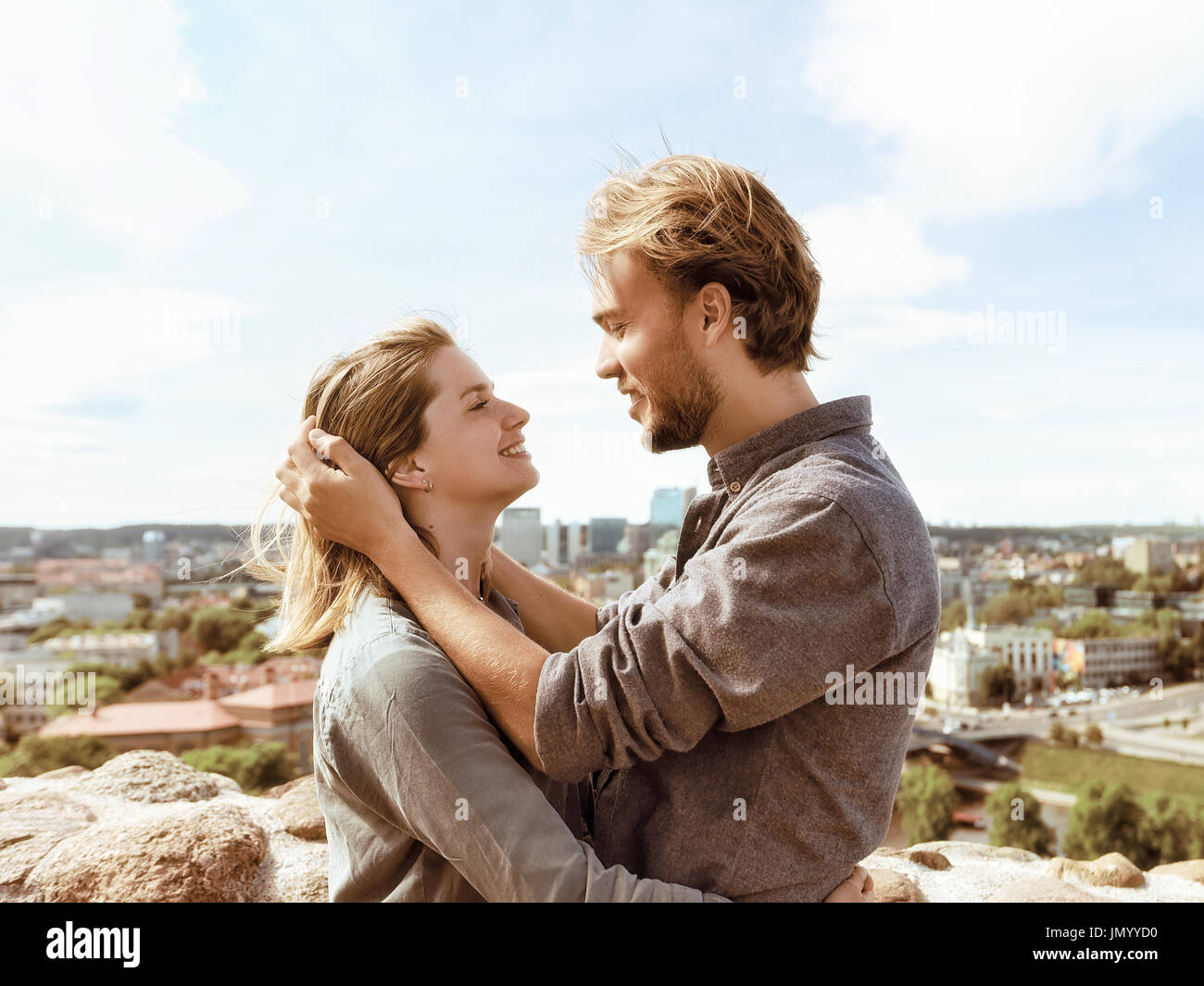 Young couple looking tenderly at each other in front of city skyline. Romantic concept - Stock Image