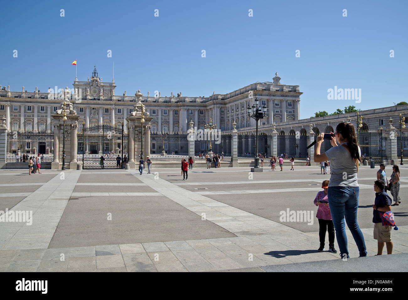 Group of tourists take photographs of Palacio Real (Royal Palace) in Madrid, Spain, in a very sunny day with unclouded blue sky. - Stock Image