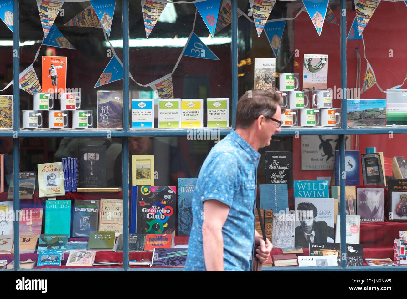 Hay on Wye man walks past bookshop window display Wales UK - Stock Image