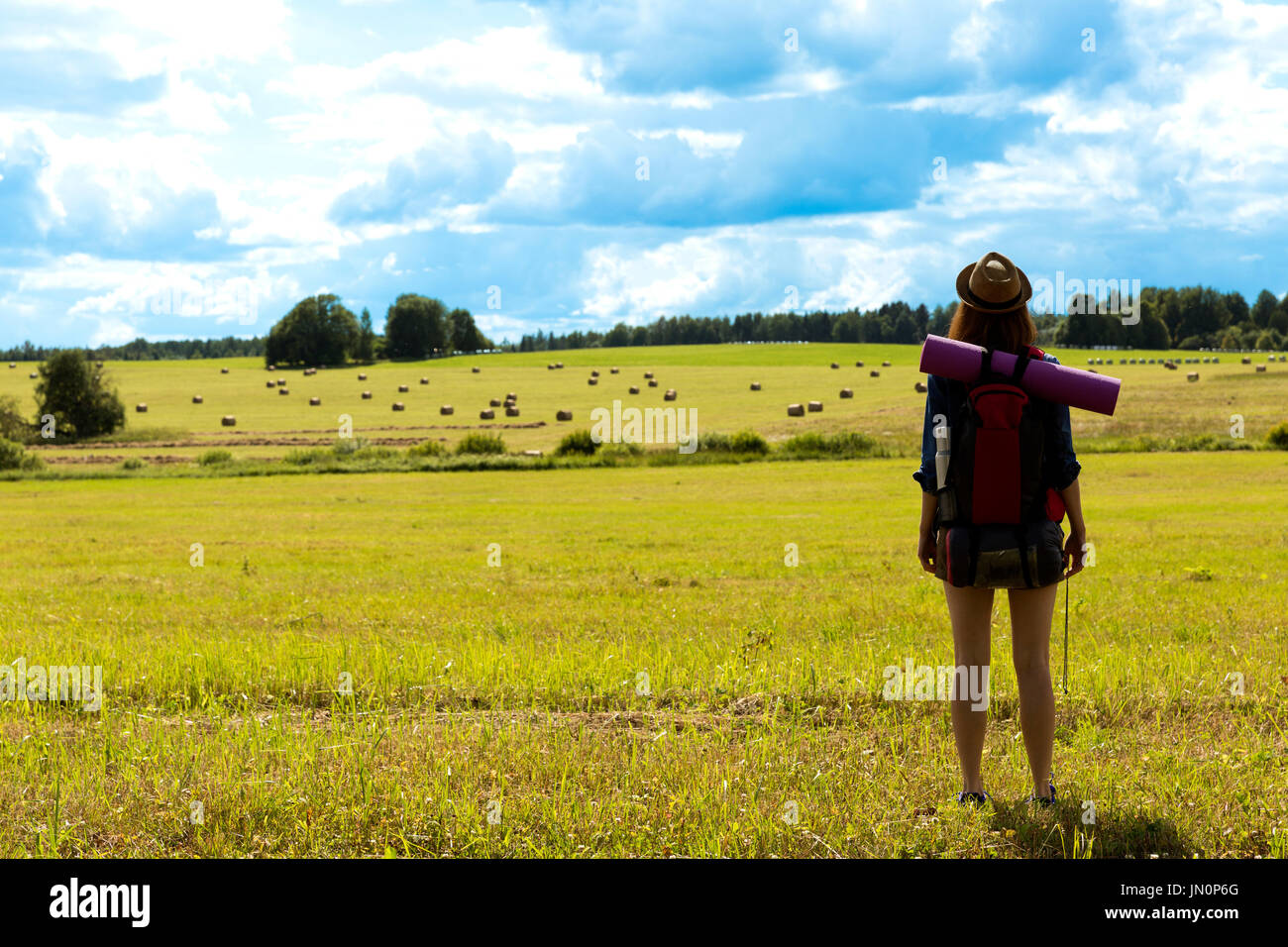 Young woman with backpack hiking in the countryside. Stress free travel concept. - Stock Image