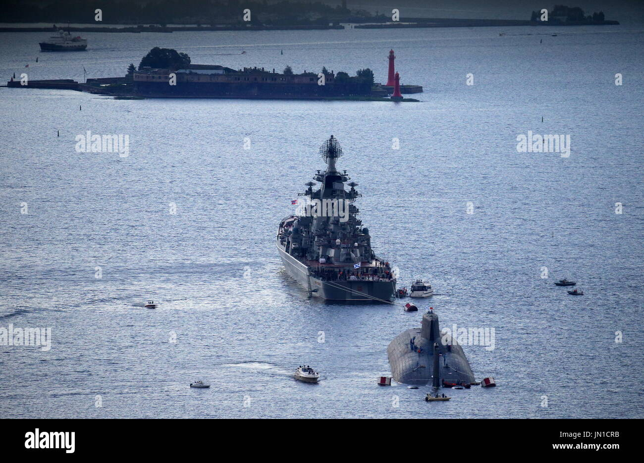 St Petersburg, Russia. 28th July, 2017. Russian Navy's TK-208 Dmitry Donskoy nuclear submarine and Pyotr Velikiy battlecruiser arrive at the Leningrad Naval Base of the Russian Baltic Fleet in the town of Kronstad on Kotlin Island to participate in the Main Navy Parade scheduled for July 30, 2017 to mark Russian Navy Day. Credit: Peter Kovalev/TASS/Alamy Live News - Stock Image