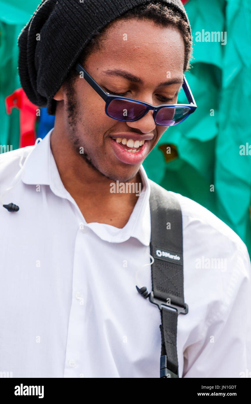 Young black man, afro-Caribbean, 20s, playing guitar. Member of the band Generation Uncovered performing outdoors at the Ramsgate Festival. - Stock Image