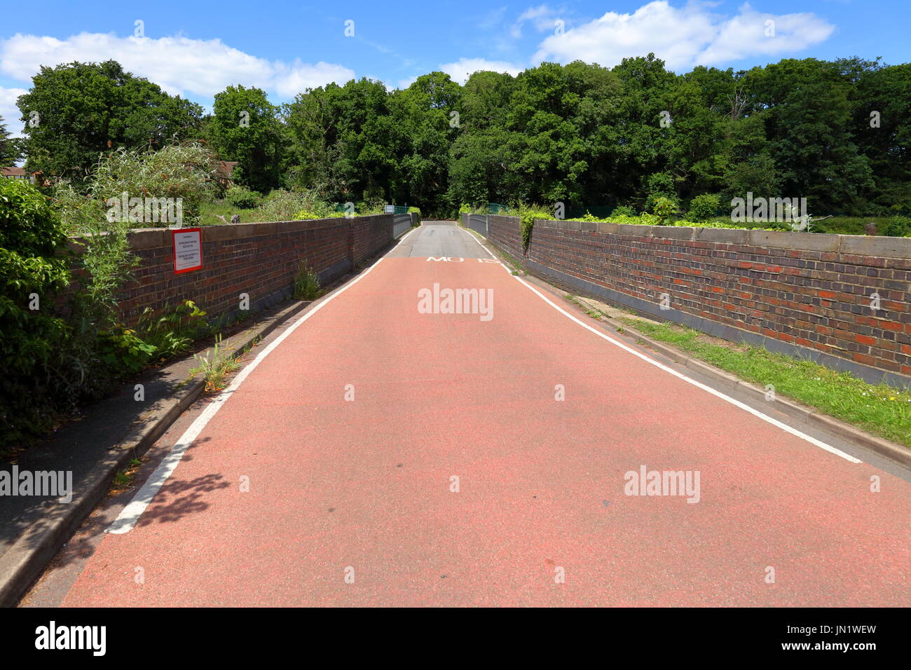 A roadway crossing the Great Western Railway at Sonning cutting over the Warren road steel bridge with its new road surface. - Stock Image